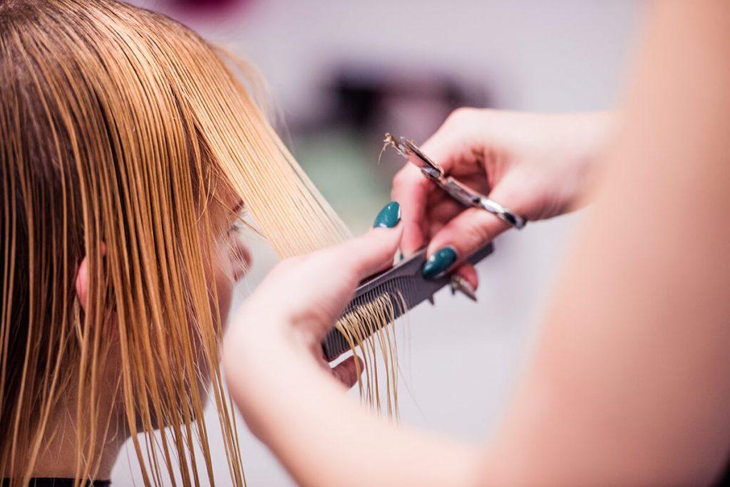 Hairstylist giving a woman a haircut in a hair salon